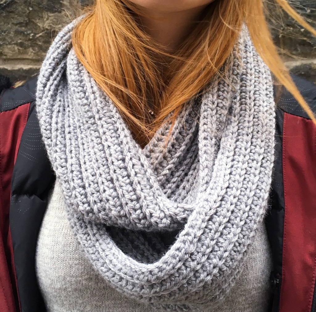 Picture of a female's torso wearing a grey crochet infinity scarf and red winter jacket.